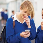 Students in school corridor with phone